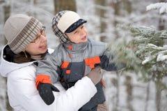 Muchacho con la mama en bosque del invierno Imagen de archivo libre de regalías