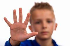 Muchacho con la mano aumentada que hace gesto de la parada imagen de archivo libre de regalías