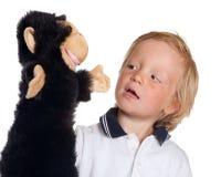 Muchacho con la marioneta del mono Fotos de archivo