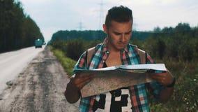 Muchacho con la mochila que mira en mapa el borde de la carretera hitchhiking Árbol en campo Viajes almacen de video