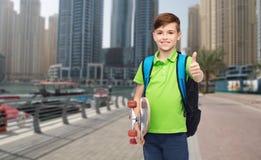 Muchacho con la mochila y el monopatín que muestran los pulgares para arriba Foto de archivo libre de regalías