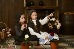 Muchacho con la muchacha en el vestido del vintage que se sienta en la tela escocesa en la caja mirada de las flores en potes Fotografía de archivo libre de regalías