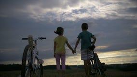 Muchacho con la muchacha con las bicicletas en la montaña que lleva a cabo las manos por la tarde almacen de metraje de vídeo