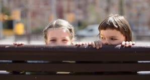 Muchacho con la muchacha rubia que oculta en un banco de la calle Imágenes de archivo libres de regalías