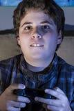 Muchacho con la palanca de mando que juega al juego de ordenador en casa. Foto de archivo