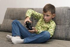 Muchacho con la palanca de mando que juega al videojuego en casa Imagen de archivo libre de regalías