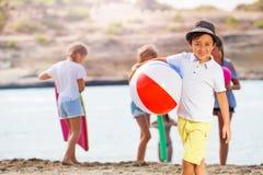 Muchacho con la pelota de playa y los amigos cerca del mar Foto de archivo libre de regalías