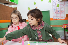 Muchacho con la pintura de la muchacha en el escritorio de la sala de clase Foto de archivo