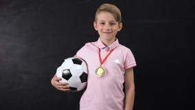 Muchacho con la situación de la bola y de la medalla cerca de la pizarra, ganador de la competencia del fútbol almacen de video