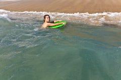Muchacho con la tabla hawaiana en el océano Foto de archivo