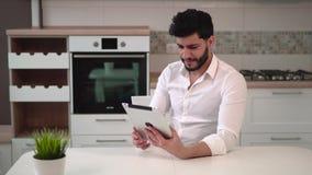 Muchacho con la tableta en cocina almacen de video