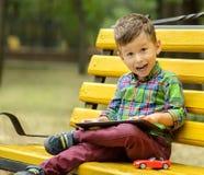 Muchacho con la tableta en parque Fotos de archivo libres de regalías