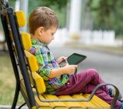 Muchacho con la tableta en parque Fotografía de archivo