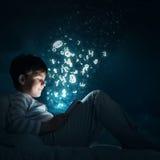 Muchacho con la tableta en su cama Fotos de archivo
