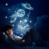 Muchacho con la tableta en su cama Fotografía de archivo