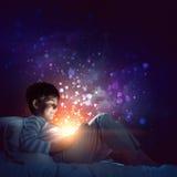 Muchacho con la tableta en su cama Imágenes de archivo libres de regalías