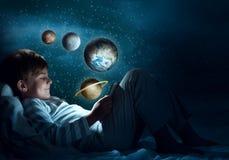 Muchacho con la tableta en su cama Imagenes de archivo