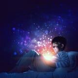 Muchacho con la tableta en su cama Imagen de archivo