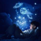 Muchacho con la tableta en su cama Fotos de archivo libres de regalías