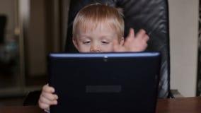Muchacho con la tableta que habla en Skype con la abuela almacen de metraje de vídeo