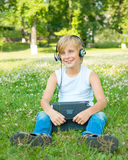 Muchacho con la tableta y los auriculares Fotos de archivo