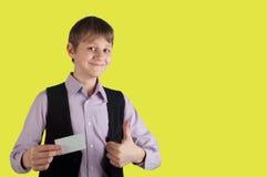 Muchacho con la tarjeta de crédito en fondo amarillo Fotografía de archivo libre de regalías