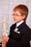 Muchacho con la vela en el día de la primera comunión santa Fotos de archivo