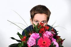 Muchacho con las flores Foto de archivo libre de regalías