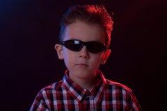 Muchacho con las gafas de sol en luces del partido Fotos de archivo libres de regalías