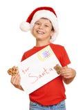 Muchacho con las galletas para santa, concepto de la Navidad de las vacaciones de invierno Imagen de archivo