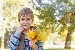muchacho con las hojas de otoño Fotos de archivo libres de regalías