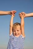 Muchacho con las manos de los padres Imagen de archivo libre de regalías