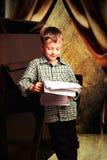 Muchacho con las notas en sus manos que se colocan alrededor del piano Fotografía de archivo libre de regalías