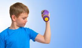 Muchacho con las pesas de gimnasia que miran el músculo del bíceps Foto de archivo libre de regalías