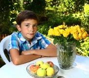 muchacho con las rosas en fondo floreciente del jardín Fotografía de archivo libre de regalías