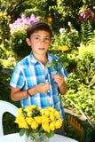 muchacho con las rosas en fondo floreciente del jardín Imagenes de archivo