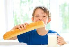 Muchacho con leche y el pan largo Fotos de archivo libres de regalías