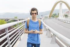 Muchacho con los auriculares en el puente Fotografía de archivo