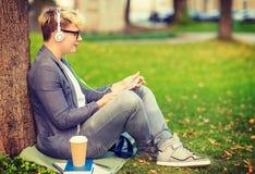Muchacho con los auriculares, PC de la tableta, los libros y el café Imagen de archivo