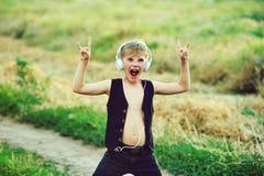 Muchacho con los auriculares que escucha la música en naturaleza Imagen de archivo libre de regalías