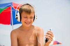 Muchacho con los auriculares usando un smartphone en la playa Imagenes de archivo