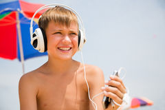 Muchacho con los auriculares usando un smartphone en la playa Imágenes de archivo libres de regalías