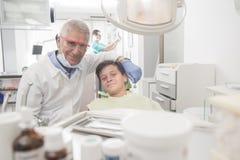 Muchacho con los dientes perfectos en el dentista Imagen de archivo libre de regalías