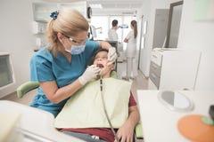 Muchacho con los dientes perfectos felices en el dentista Fotos de archivo