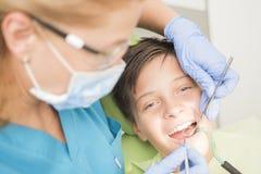 Muchacho con los dientes perfectos felices en el dentista Imagenes de archivo