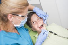 Muchacho con los dientes perfectos felices en el dentista Imagen de archivo libre de regalías