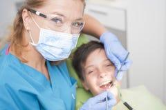 Muchacho con los dientes perfectos felices en el dentista Fotografía de archivo libre de regalías