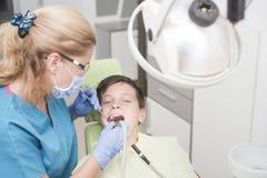 Muchacho con los dientes perfectos felices en el dentista Fotos de archivo libres de regalías