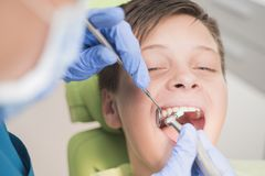 Muchacho con los dientes perfectos felices en el dentista Foto de archivo libre de regalías