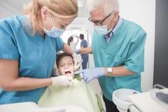 Muchacho con los dientes perfectos felices en el dentista Foto de archivo